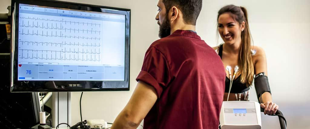 Frau macht Belastungs EKG mit Elektroden auf dem Körper daneben Monitor und Arzt